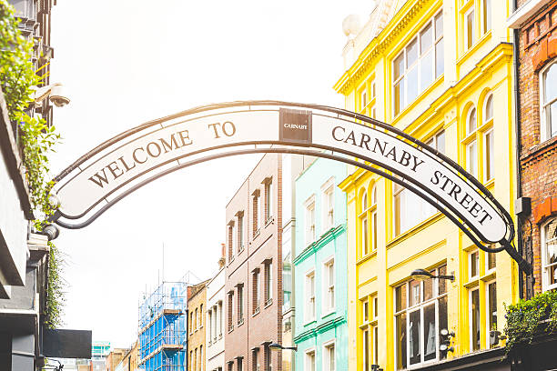 Carnaby street sign in London Carmaby street sign in London with some colorful houses on background and sun beams from top. This is a famous place in London, with many tourists visiting every day. carnaby street stock pictures, royalty-free photos & images