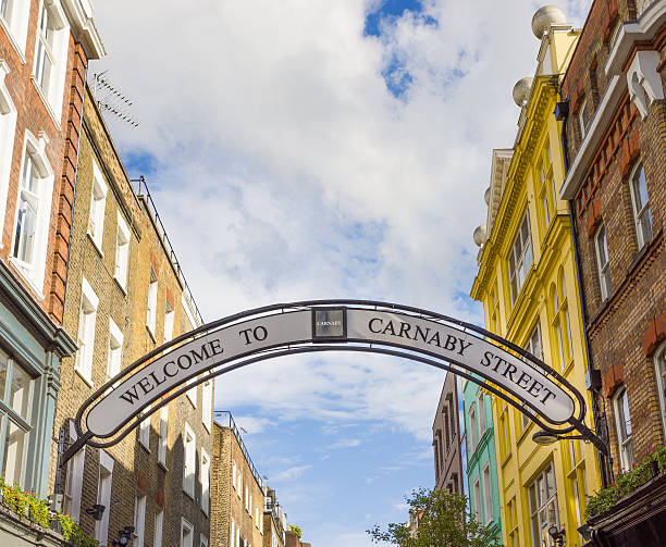 Carnaby Street sign A banner over Carnaby Street in Soho, London. carnaby street stock pictures, royalty-free photos & images
