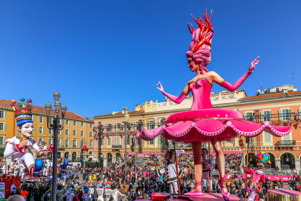 Carnaval de Nice, This years theme King of Cinema (ROI du Cinéma)  - Bright pink ballerina and king of the carnaval moving in the show stock photo