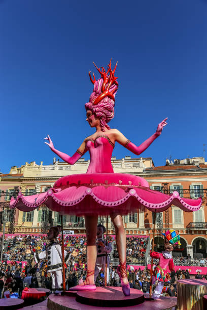 Carnaval de Nice, This years theme King of Cinema (ROI du Cinéma)  - Close up of pink ballerina in amoungst the stands of people with clown assistants below her tutu stock photo