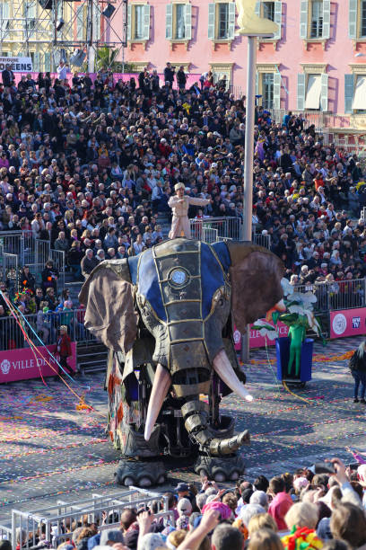 Carnaval de Nice, This years theme King of Cinema (ROI du Cinéma) -  focus on man dancing on mechanical elephant stock photo