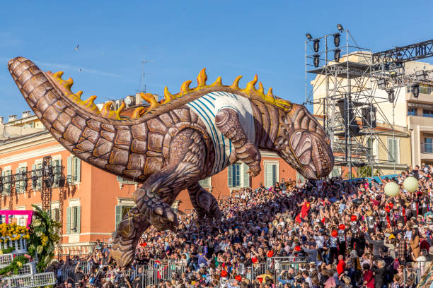 Carnaval de Nice, This years theme King of Fashion -  Giant dinosaur balloon floats into the seated crowds stock photo