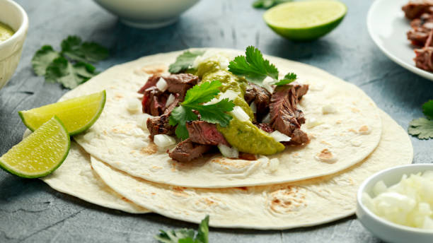 Carne Asada Tacos with grilled steak, green sauce and onion. Mexican food stock photo