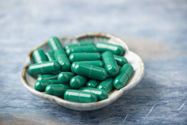 l-carnitin kapseln. konzept für eine gesunde nahrungsergänzung. rustikale holzhintergründe. platz kopieren. - grüner tee kapseln stock-fotos und bilder
