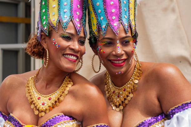 Carnival celebration event at Curacao, colourful dressed woman smiling during parade Willemstad, Curacao - February 11, 2018: portrait of two joyful women dressing colourful costumes during the traditional carnival parade (Grand carnival parade) at the caribbean island of Curacao. Thousands of people march each year at the parade, dancing through the streets of Willemstad, wearing colourful clothes and having lot of fun. afro caribbean ethnicity stock pictures, royalty-free photos & images