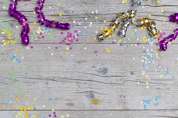 carnival confetti on wood background - motto stock-fotos und bilder