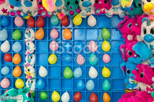 The object of the carnival game shown here is to toss a dart to pop the balloons in the grid.  Surrounding the balloons are some of the colorful prizes you can win which include some giant stuffed animals.