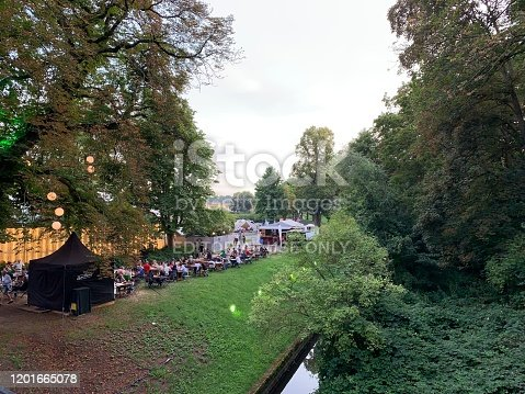 Kassel, Germany - August, 5 - 2019:  Carnival in the public park Karlsaue. People sitting in a outdoor restaurant in the background.