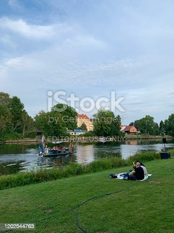 Kassel, Germany - August, 5 - 2019:  Carnival in the public park Karlsaue. People on the meadow and a small sightseeing ship on the river.