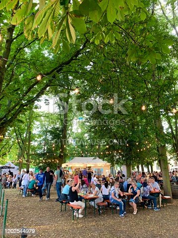 Kassel, Germany - August, 5 - 2019:  Carnival in the public park Karlsaue. People sitting in an outdoor restaurant.