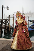 Venice, Italy, 31 January 2016:  Woman with umbrella on the venetian lagoon background. Venetian carnival outfit.
