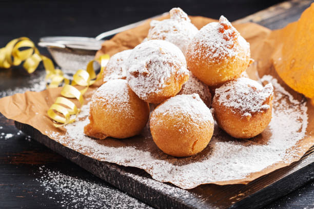 Carnival italian fritters in carnival on black wooden board. Carnival italian fritters in carnival on black wooden board. fritter stock pictures, royalty-free photos & images