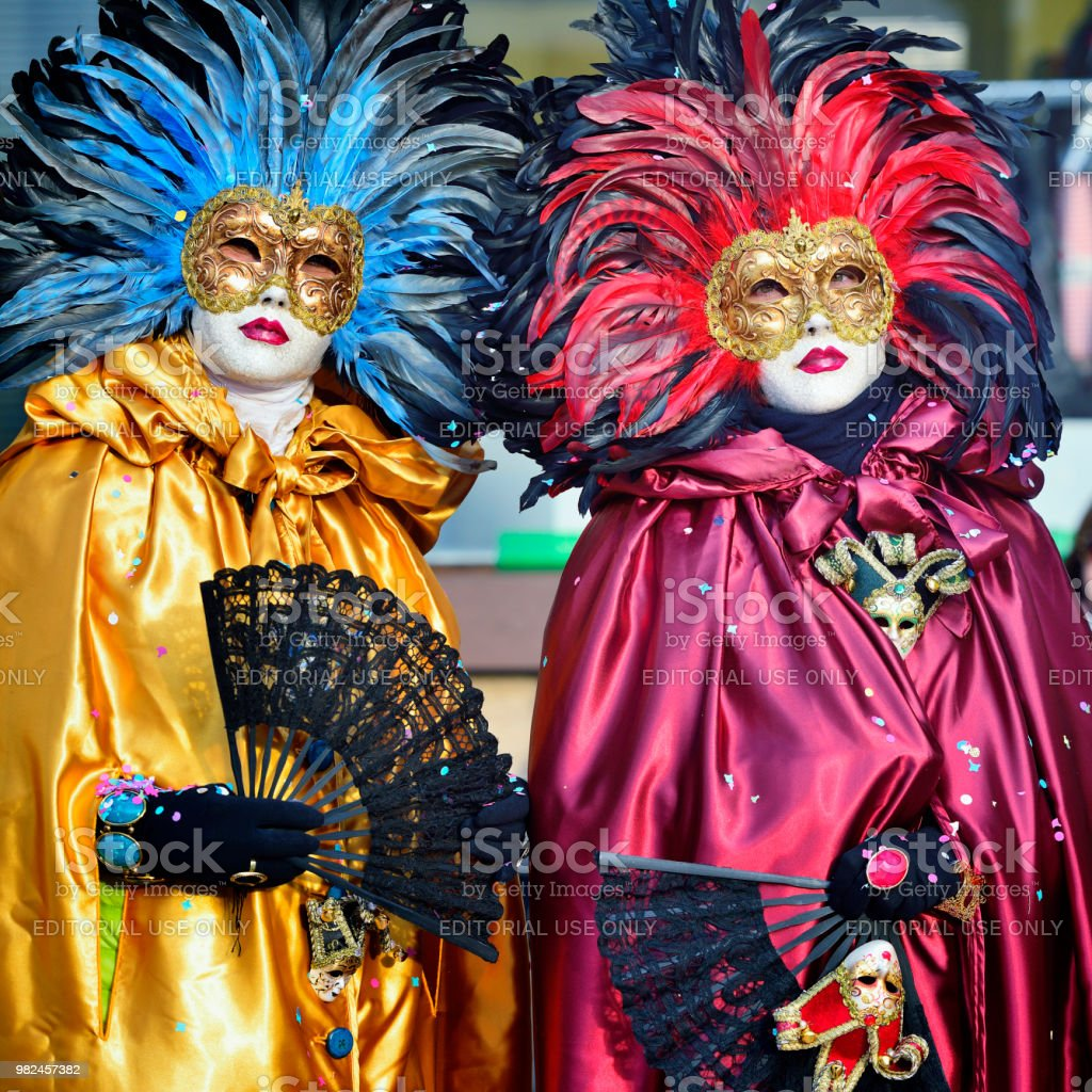 The people posing wearing a feather Carnival mask and traditional...