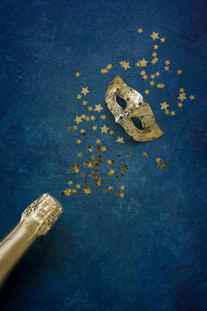 Máscara de carnaval, garrafa de champanhe e confete de glitter dourado. Visão superior, Feche em fundo azul clássico. - foto de acervo