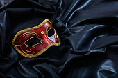 Red carnival mask isolated on black satin background