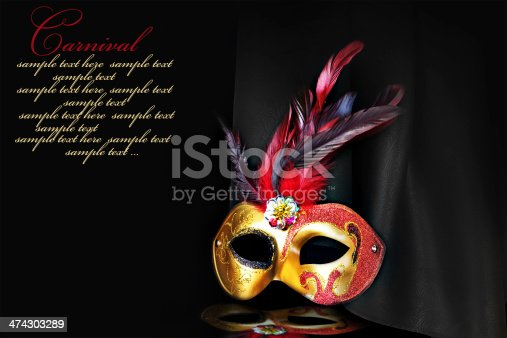 istock Carnival mask on black silk background 474303289