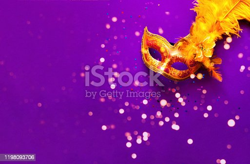 Carnival mask on purple background with sparkles. Festive backdrop for projects.Close-up. Copy space