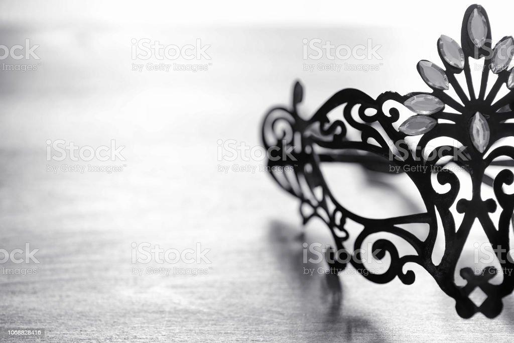 Máscara de Carnaval em cima da mesa. O assunto da camuflagem um encontro durante um carnaval. Máscara Veneziana sobre uma mesa de madeira em preto e branco. - foto de acervo