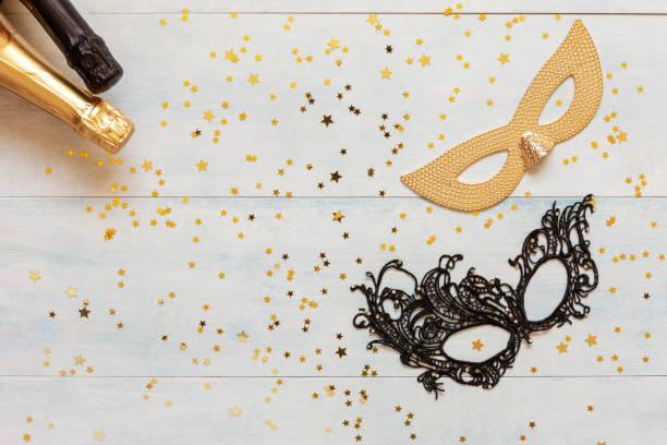 Máscaras do carnaval, frascos do champanhe e confetti do glitter do ouro. Vista superior, fim acima no fundo azul - foto de acervo
