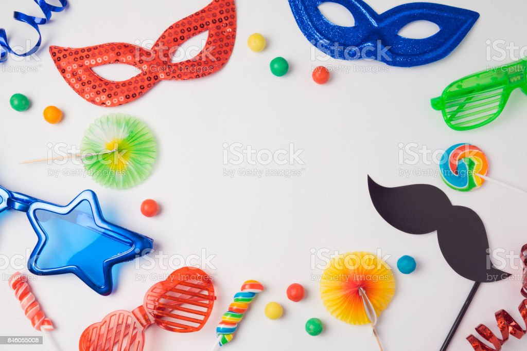 Carnival party concept with costume mask and glasses on white background. Top view from above stock photo
