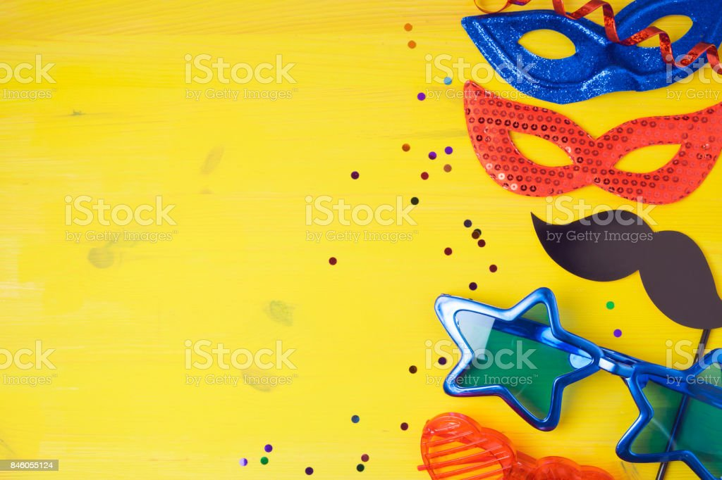 Carnival party concept with costume mask and glasses on yellow background. Top view from above stock photo