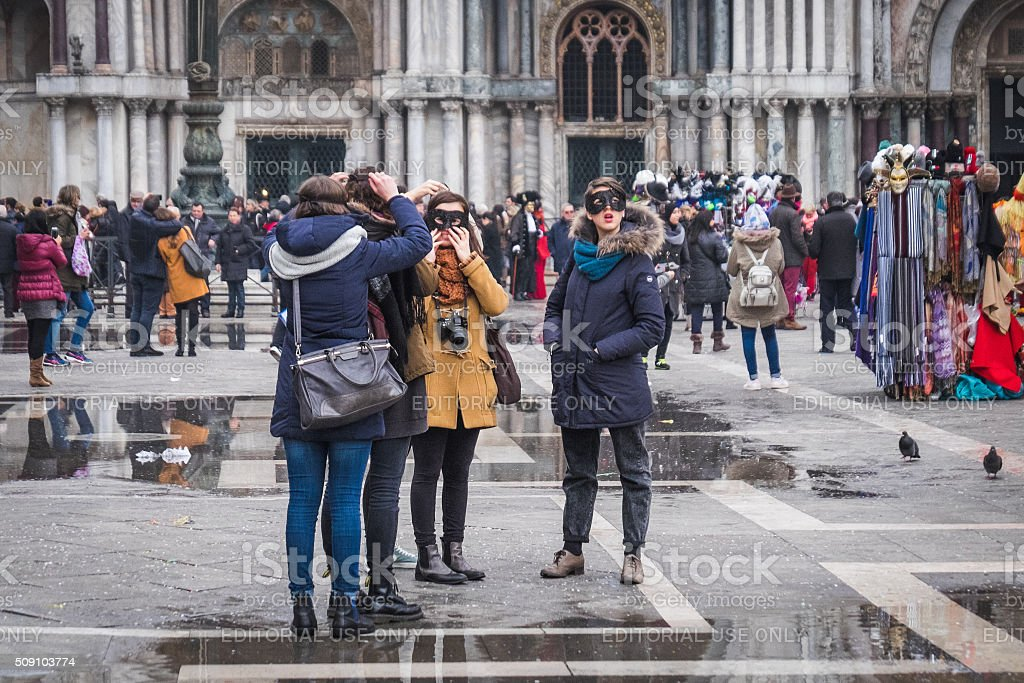 Carnival revellers adjust their masks in St Mark's Square stock photo