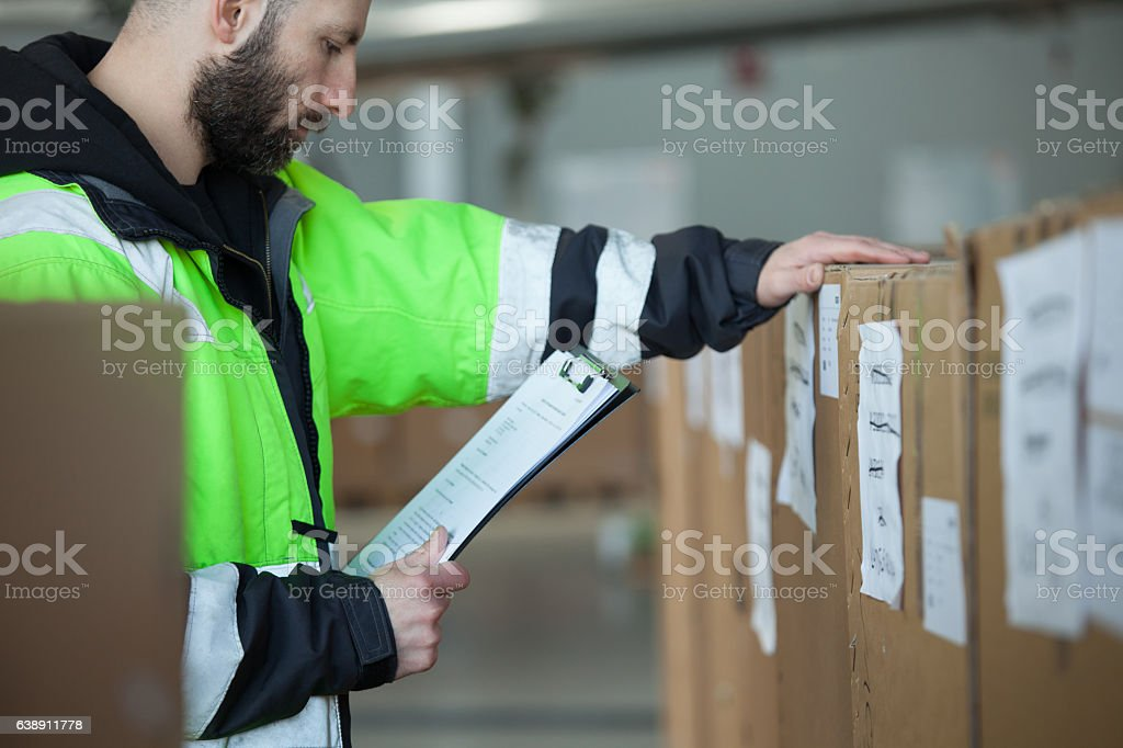 Caro men checking parcels Caro men chcecking parcels, holding clipboard in hand. Adult Stock Photo
