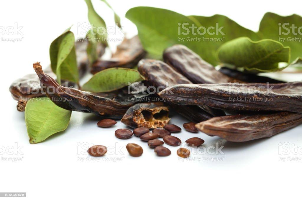 Feijão de alfarroba. Alfarroba doce orgânica saudável vagens com sementes e folhas no fundo branco - foto de acervo