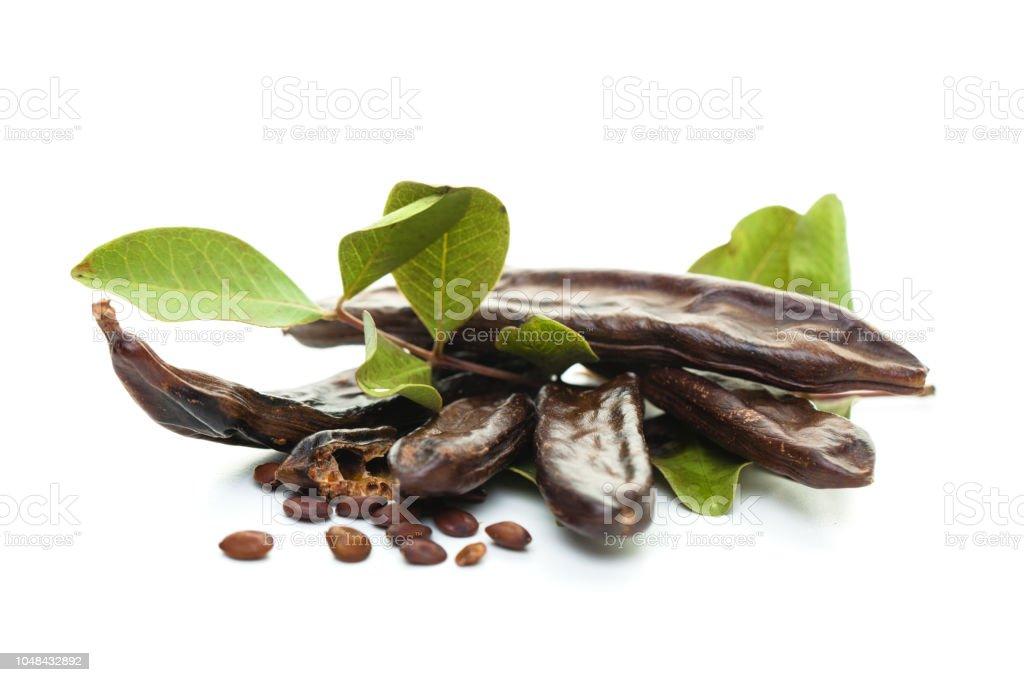 Alfarroba em fundo branco. Saudável orgânico doce de alfarroba com sementes e folhas - foto de acervo