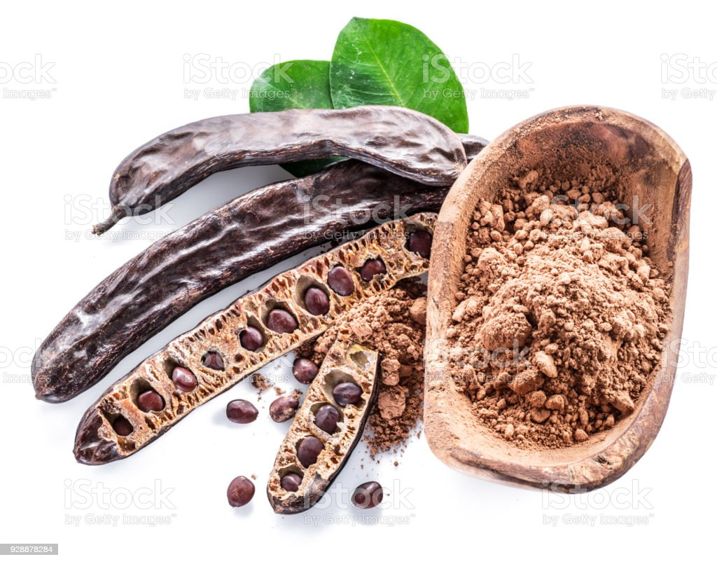 Las vainas de algarrobo y polvo de algarroba en el recipiente de madera. - foto de stock