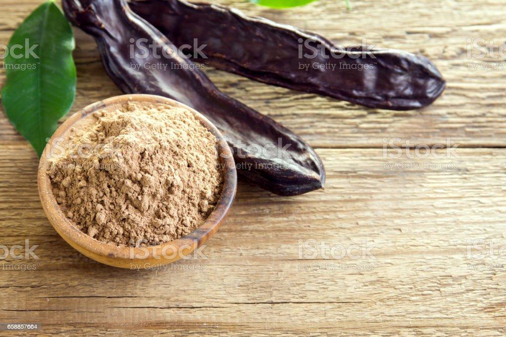 Las vainas de algarrobo y algarrobo en polvo - foto de stock