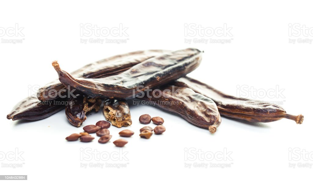 Las vainas de algarroba y semillas sobre fondo blanco - foto de stock