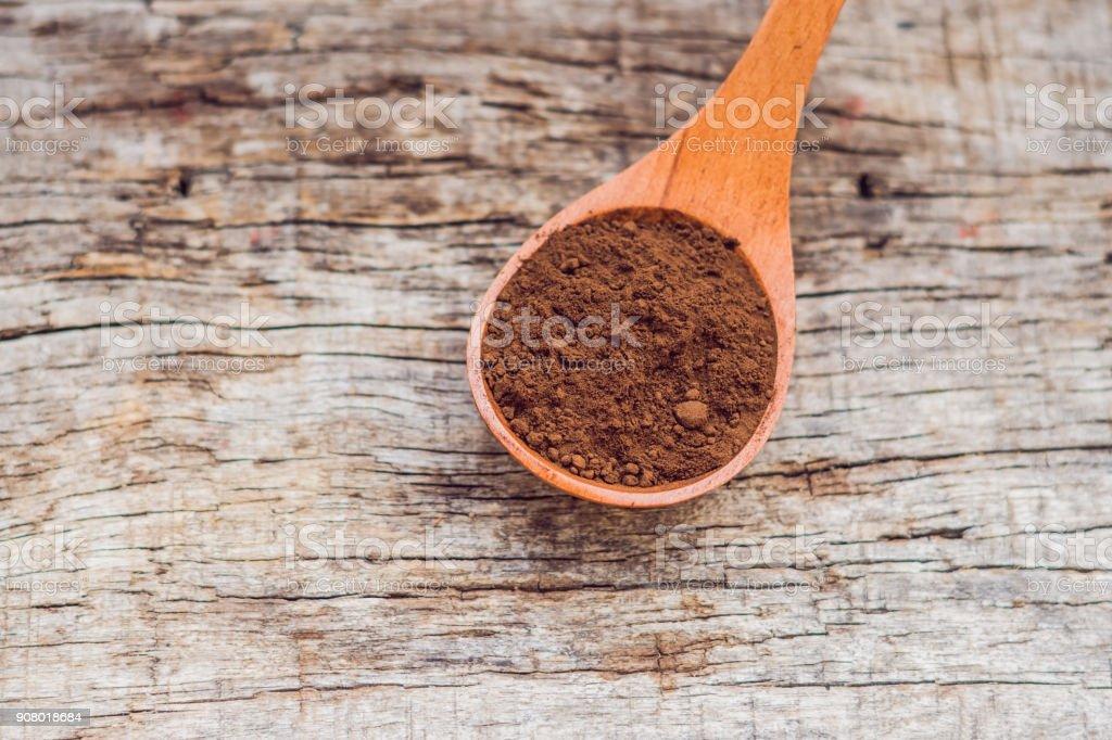 Polvo de algarroba en una cuchara de madera sobre un fondo de madera vieja - foto de stock