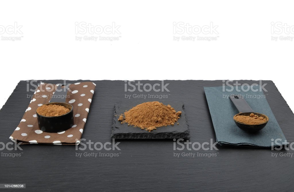 Polvo de algarroba en la medición de la cuchara en pizarra - foto de stock