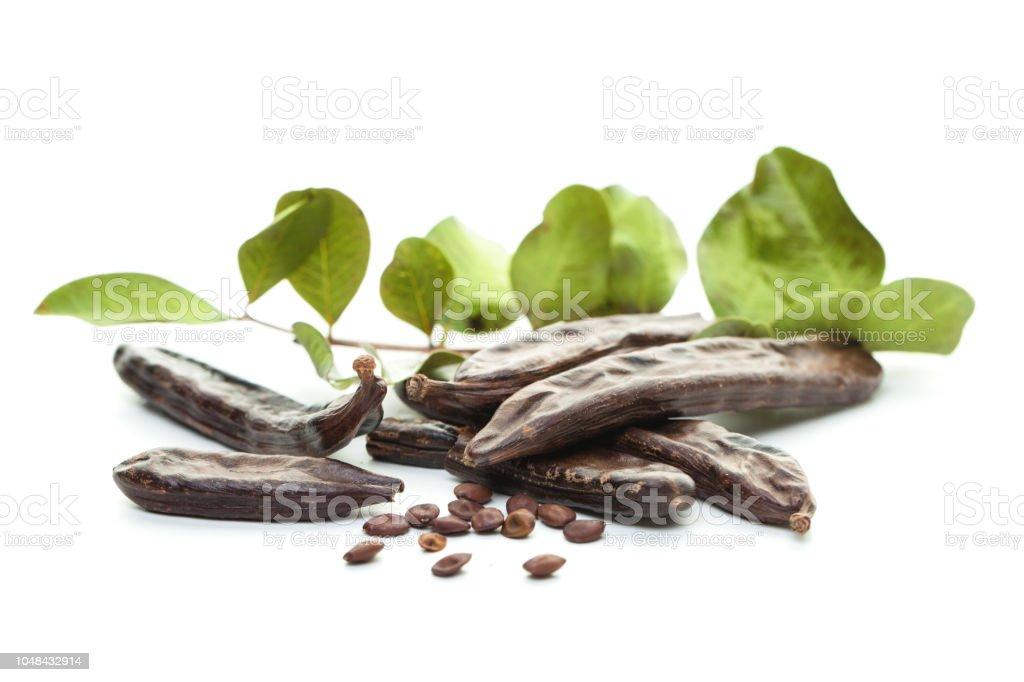 Fondo de algarrobo blanco. Vainas de algarroba orgánica con semillas y hojas verdes. Fondo de alimentos comer, sano. - foto de stock