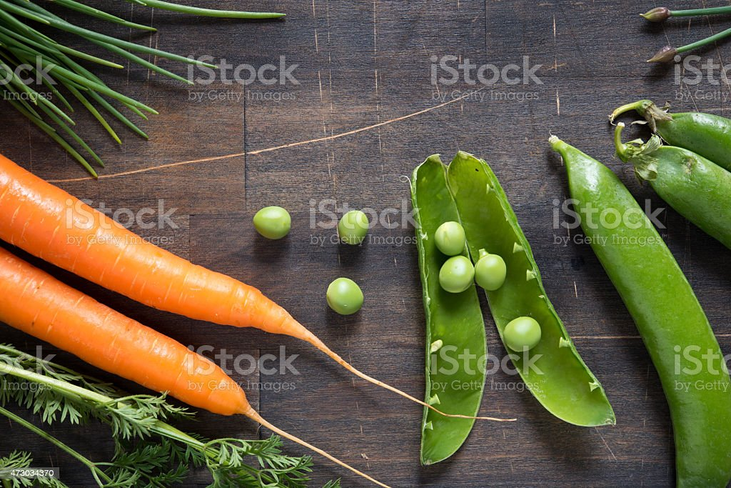 carots and snow pea on wooden kitchen table stock photo