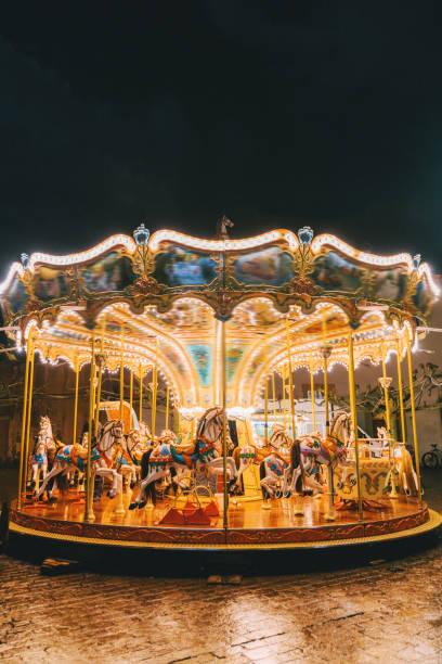 karussell in der nacht auf weihnachtsmarkt - karussell stock-fotos und bilder