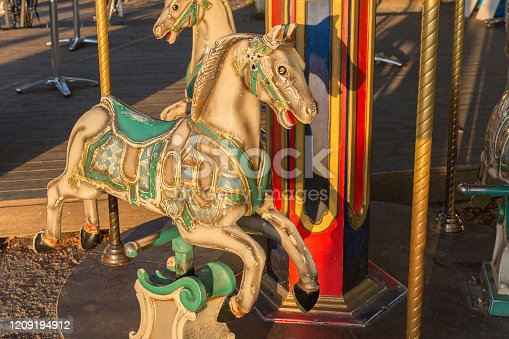 Herrsching, Bavaria / Germany - Sept 18, 2019: View on carousel horse with green saddle. Part of small merry go round / carousel at Herrsching promenade. Amusement, fun and joy for kids / children.