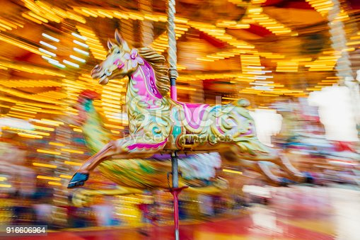 Carousel horse motion blur background as the ride spins.