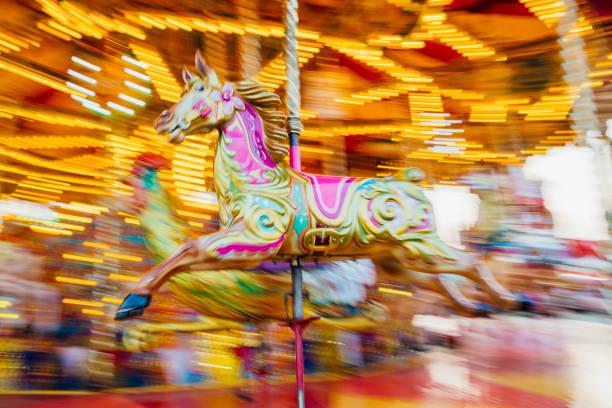 karussell-pferd mit motion blur hintergrund - karussell stock-fotos und bilder