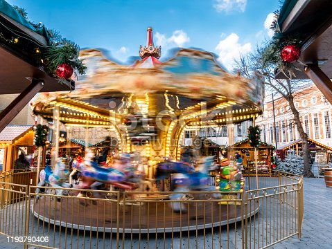 Carousel on motion outdoors in Christmas Market square at dusk in Kingston Upon Thames town in winter holiday, in London, England