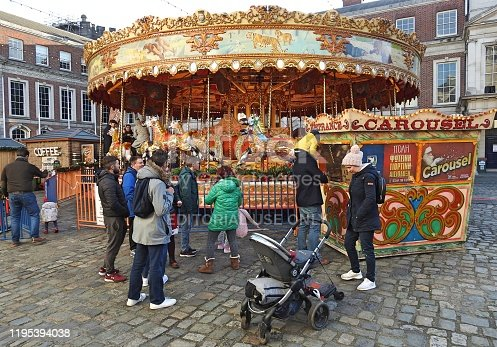 16th December 2019, Dublin, Ireland. People watching a carousel at the free to enter outdoors 'Christmas at the Castle' Christmas market at Dublin Castle off Dame Street.