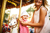Mother and baby girl on a carousel ride