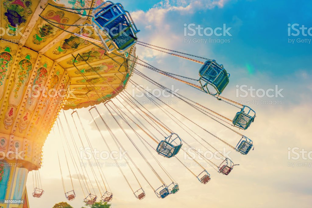 carousel ride spins fast in the air at sunset - a swinging carousel fair ride at dusk stock photo
