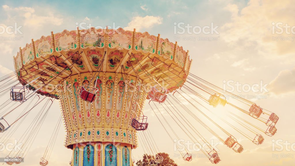 carousel ride spins fast in the air at sunset - vintage filter effects - a swinging carousel fair ride at dusk stock photo