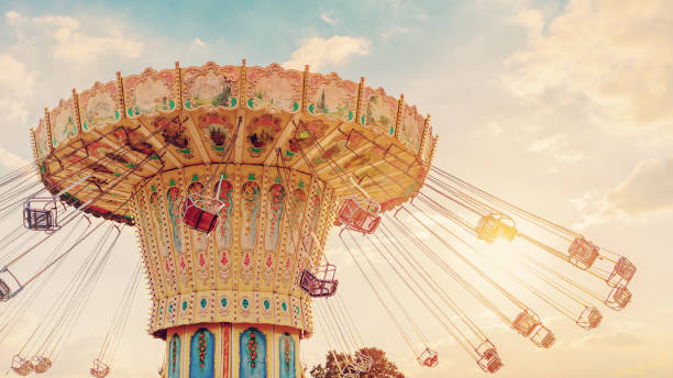carousel ride spins fast in the air at sunset - vintage filter effects - a swinging carousel fair ride at dusk - катание на аттракционах стоковые фото и изображения