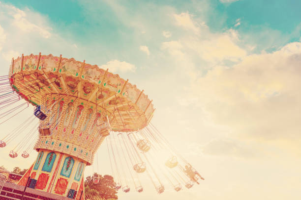 carousel ride spins fast in the air at sunset - vintage filter effects - a swinging carousel fair ride at dusk - carnival stock photos and pictures