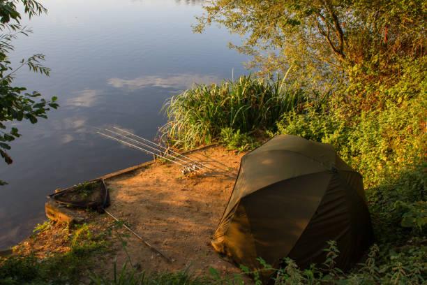 Carp Angler scenic landscape overlooking lake at Dawn stock photo