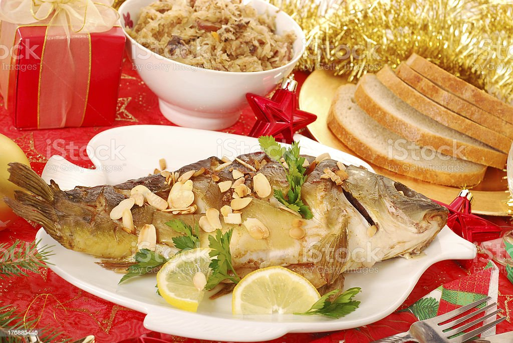 carp baked with almonds on christmas table royalty-free stock photo