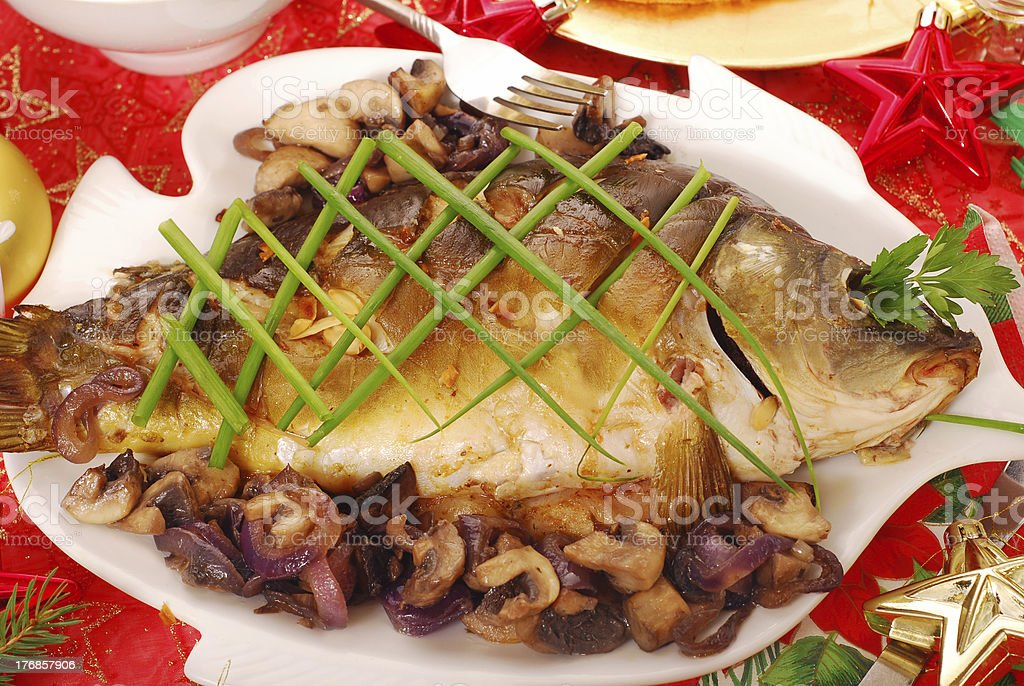 carp baked with mushrooms and onion for christmas stock photo